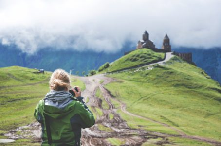 Hiker takes a photograph of a castle on the top of a lush mountain