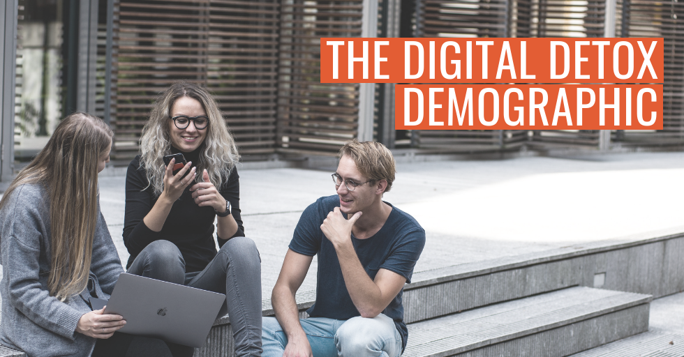 """Three people sat together on steps, smiling, with devices in their hands. Text reads, """"The digital detox demographic."""""""