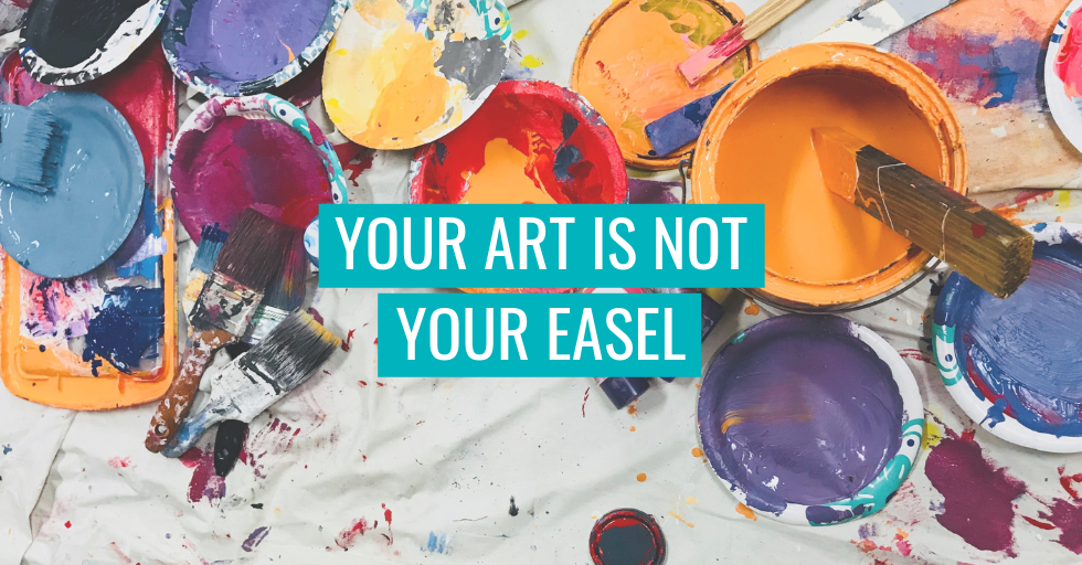 """Paint and brushes on the floor. Text reads """"Your art is not your easel"""""""