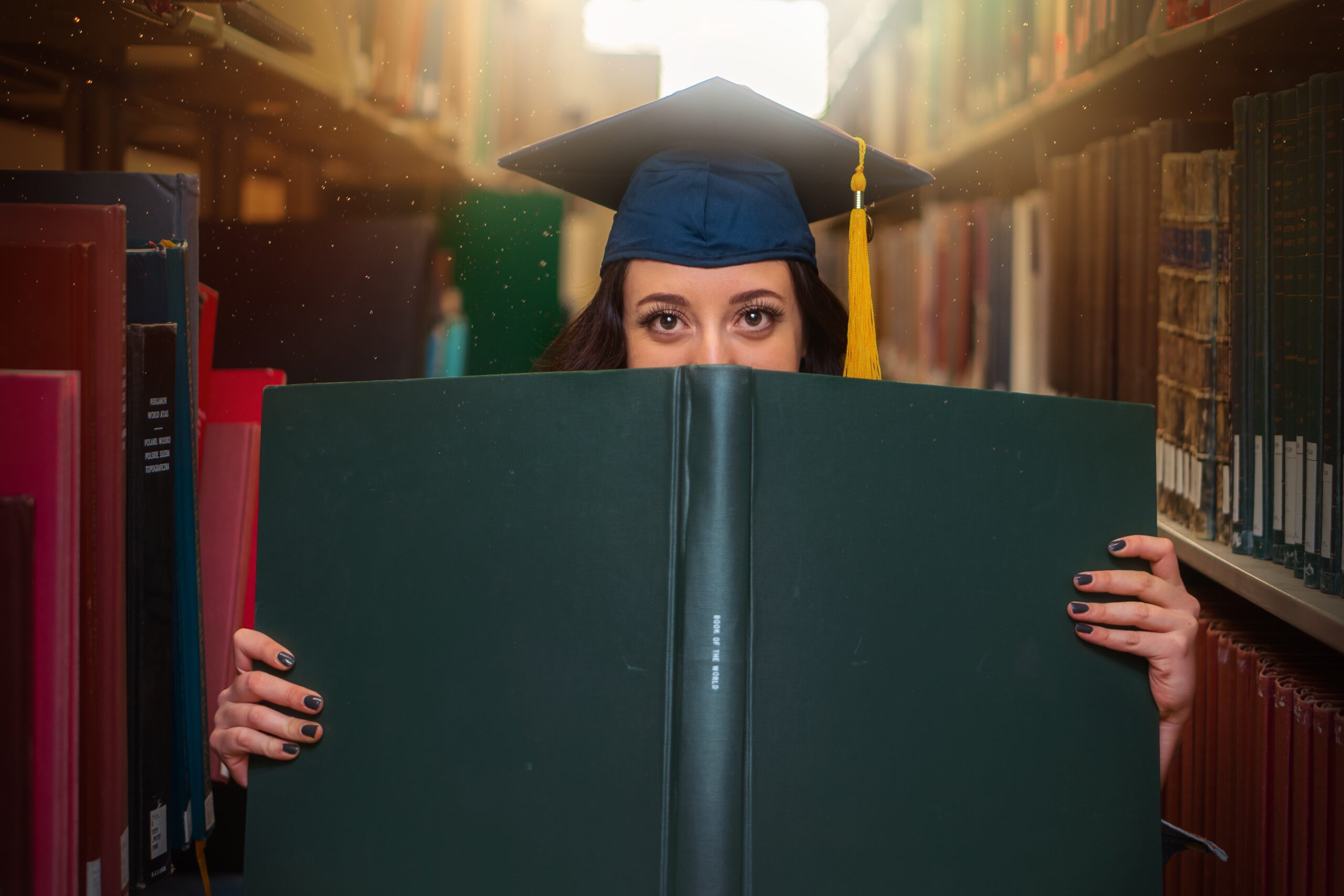 A happy student wearing a graduation cap, peering over the top of a large book, in a sunlit university library.