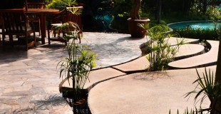 Natural Stone Pond Border Against Colored Textured Concrete