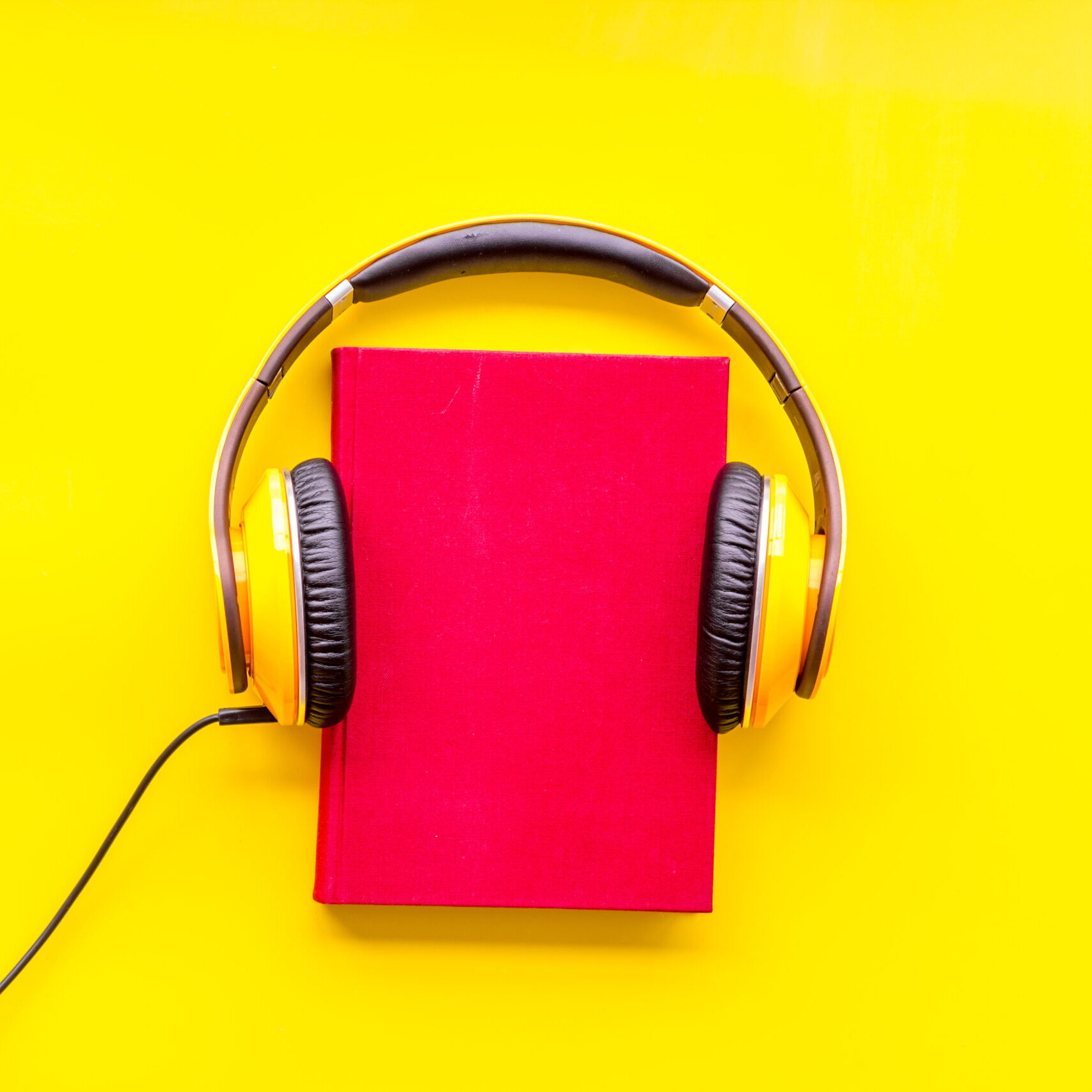 listen to audio books with headphone on yellow library desk background flatlay