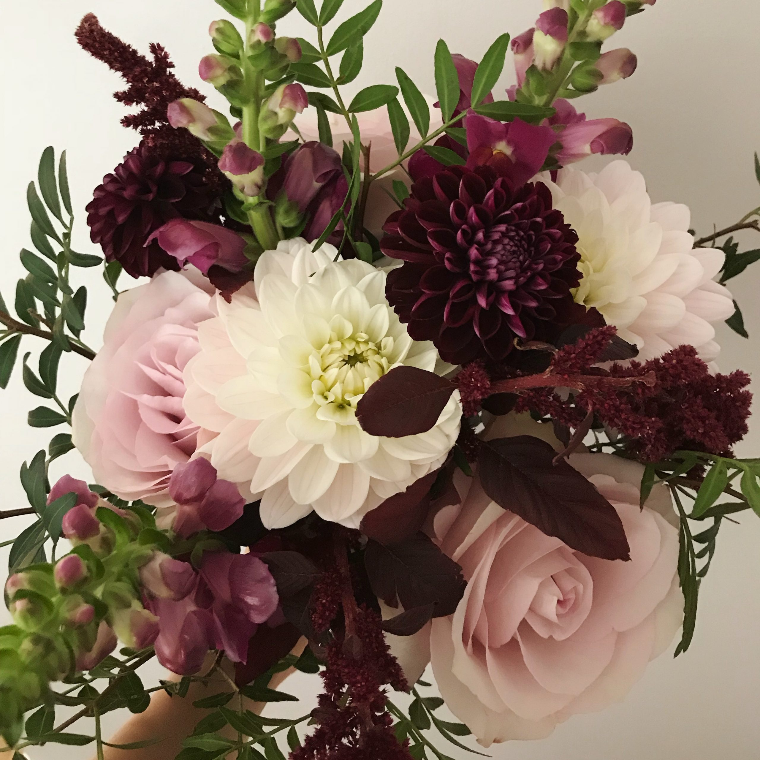 image of a floral bouquet made using roses, snap dragons and dahlias
