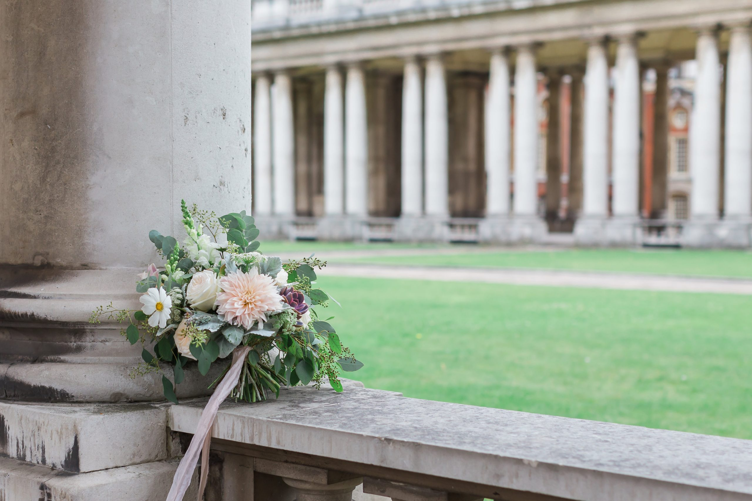 image of a bridal bouquet sitting on a wall with stone columns behind