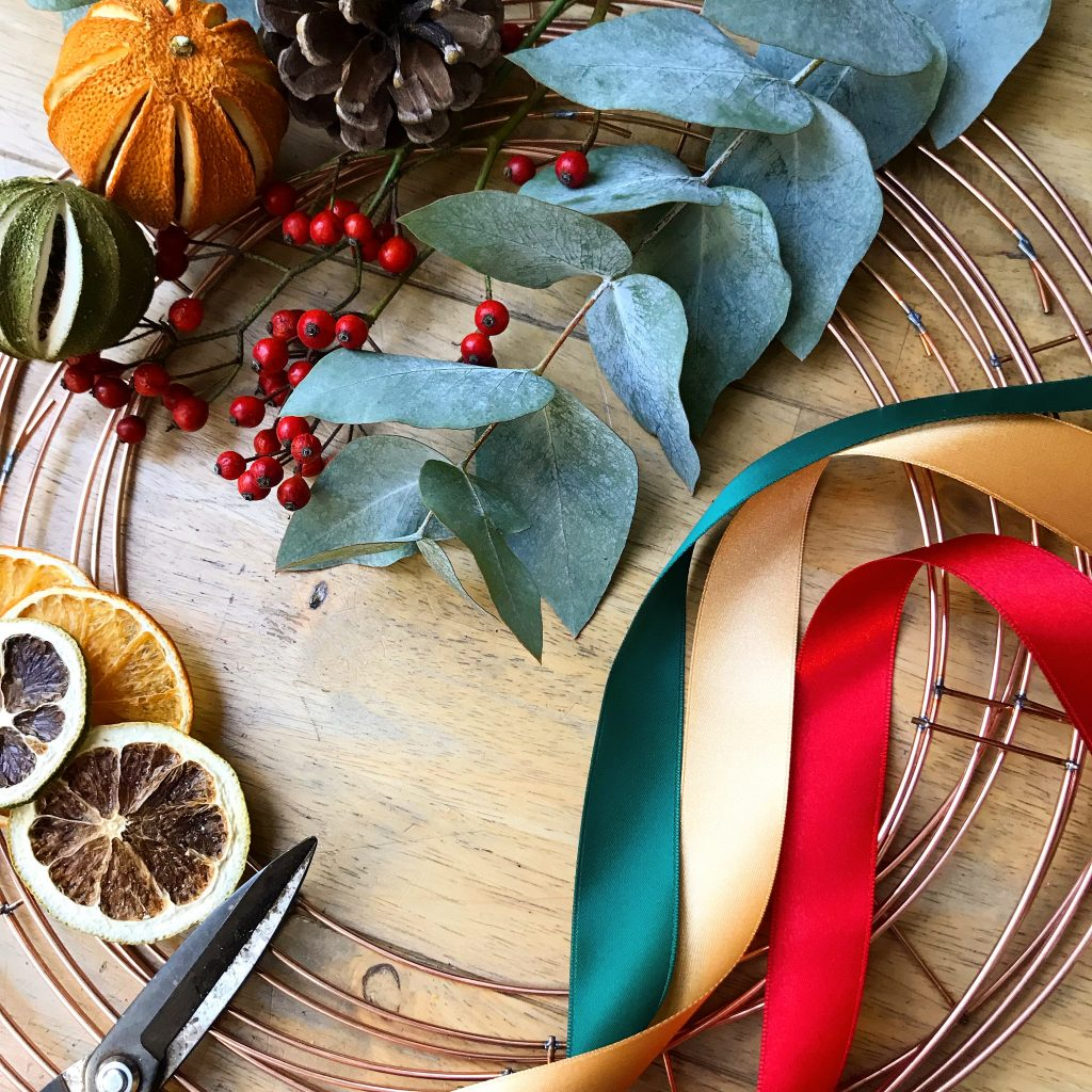 Materials used for making a wreath including wire wreath rings, ribbons, dried fruit, pine cones, scissors, eucalyptus and red berries
