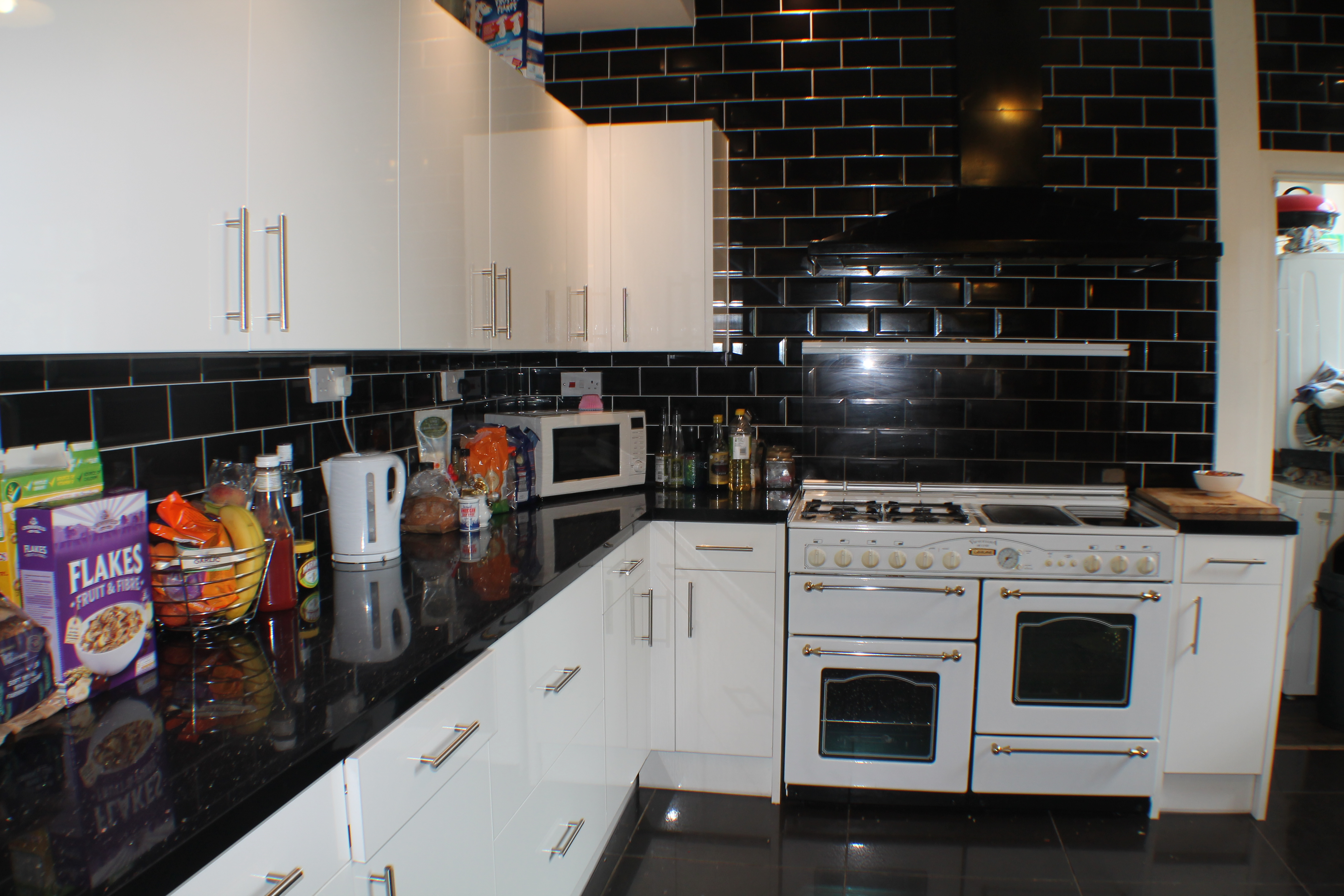 Fully equipped kitchen with oven, microwave, toaster, pots and pans.