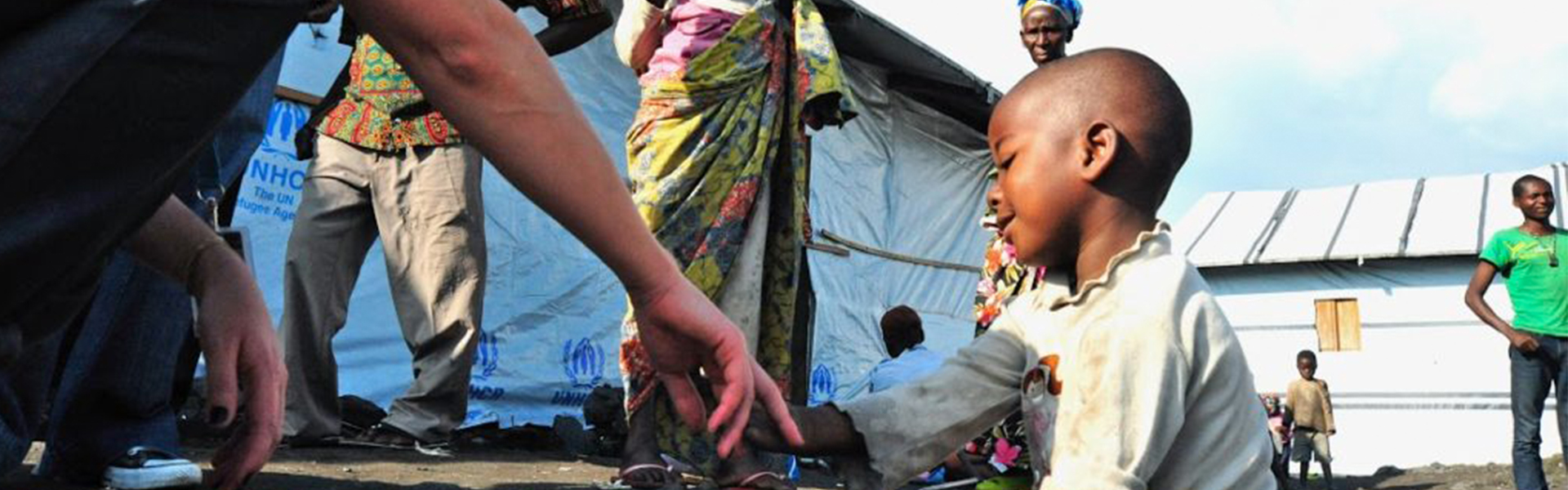 Aurelie Viard-Cretat shaking hands with a four year old beneficary of her emergency relief lead program in Congo