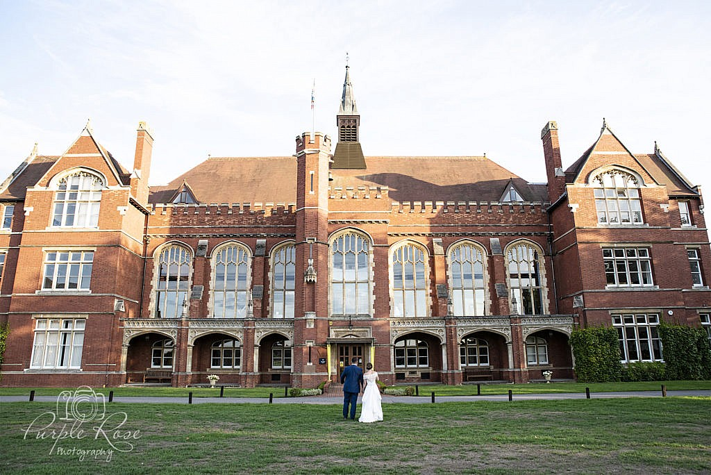 Bride & groom standing in front of their wedding venue Bedford School
