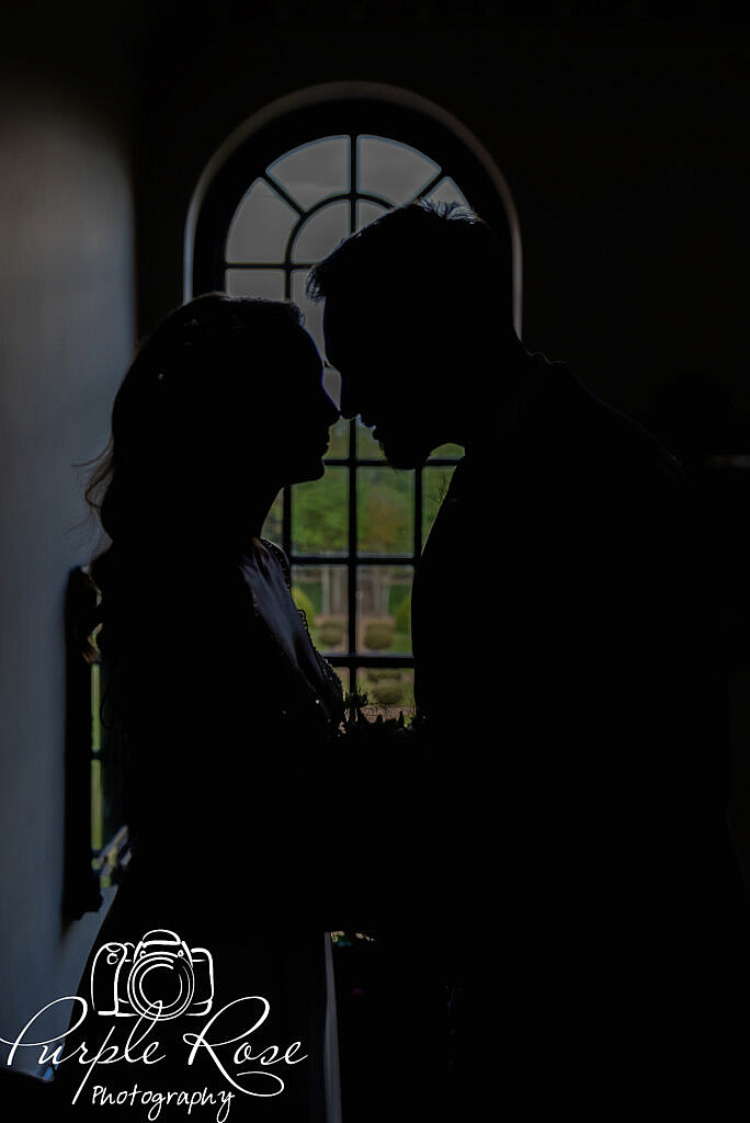 Silhouette of bride and groom in front of a window
