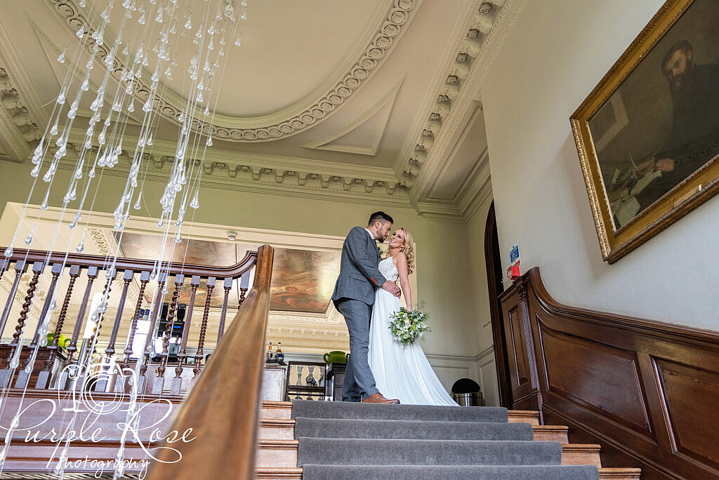 Bride and groom standing at the top of a staircase