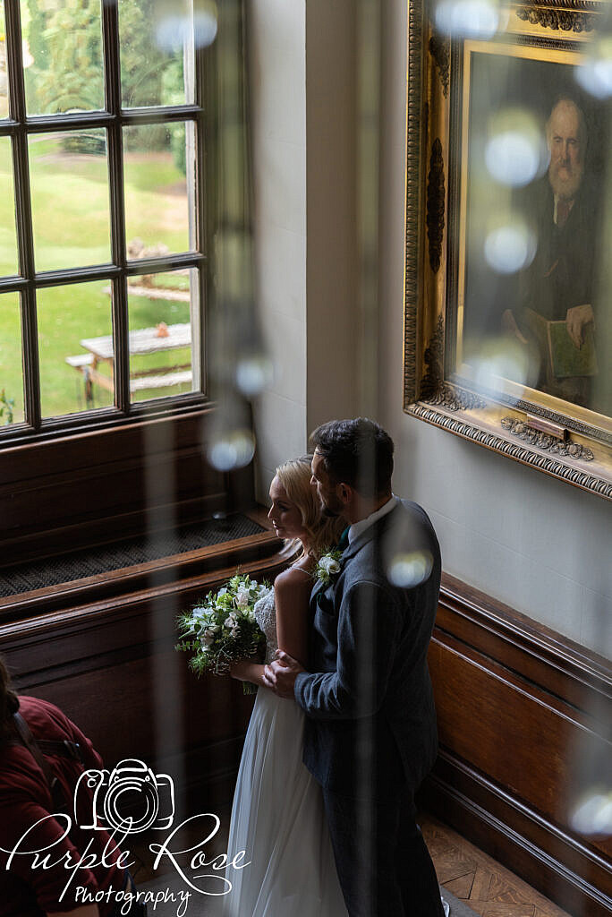 bride and groom standing by a window