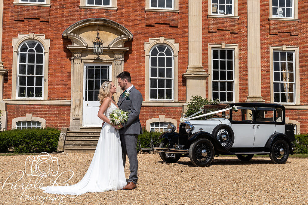 Bride and groom with wedding car and venue