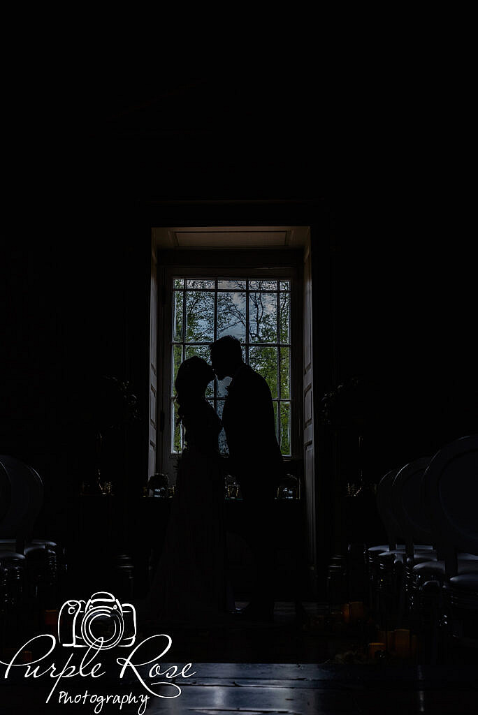 Silhouette of bride and groom in front of a large window
