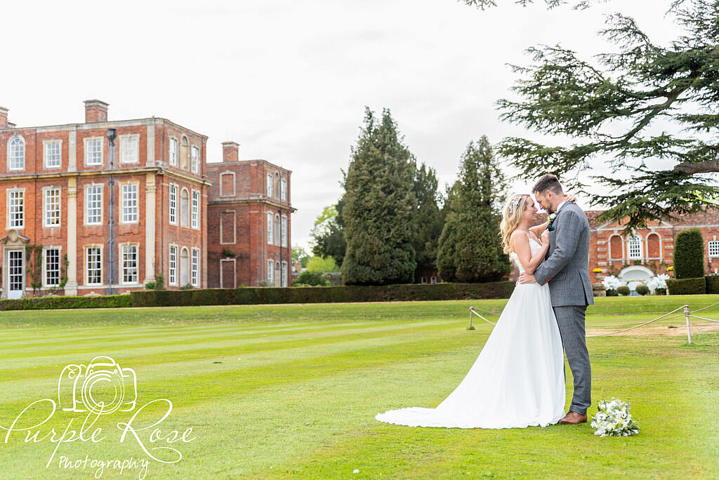 Bride and groom embracing in their wedding venues gardens