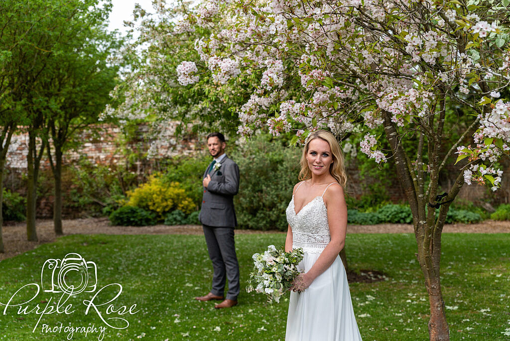 Bride smiling while her groom stand s in the background