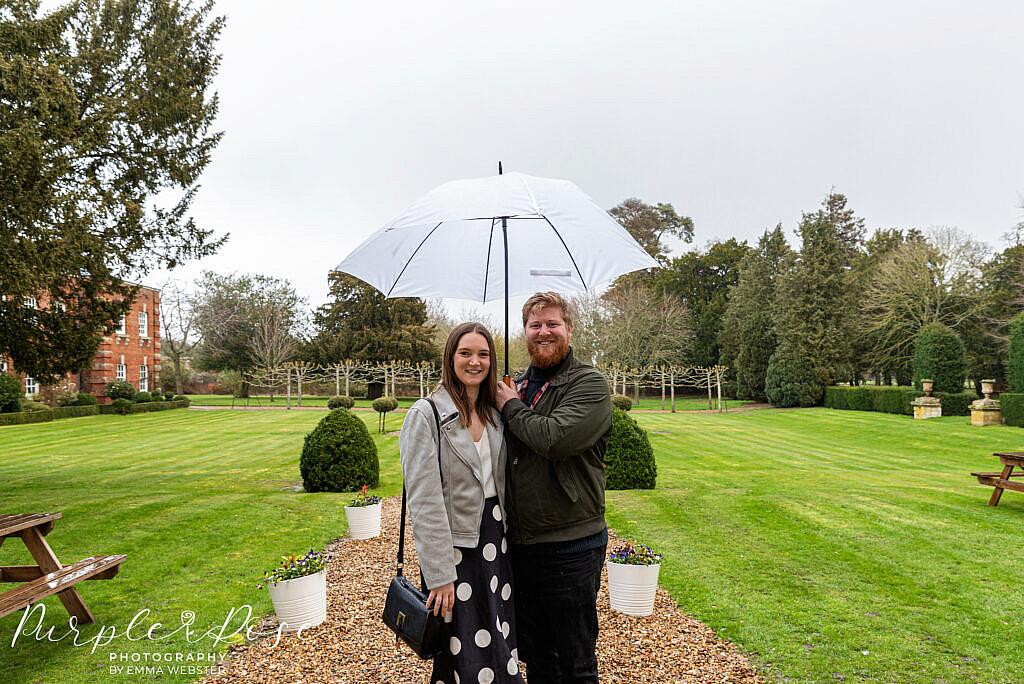 Couple sheltering under an umbrella