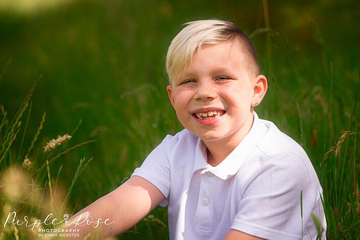 Boy sat amongst long grass