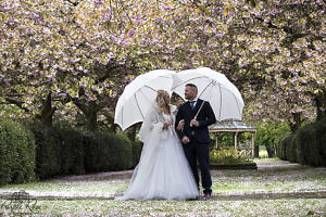 A couple enjoying the rain on their wedding day