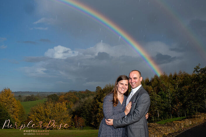 Couple in front of a rainbow