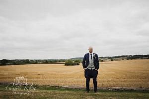 Groom standing in front of open fields