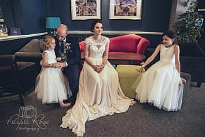 Bride, groom and their children sitting together