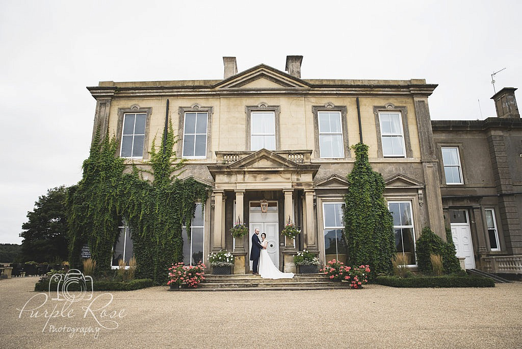 Bride and groom stood on steps of their wedding venue