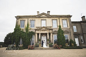Bride and groom embracing in front of their wedding venue