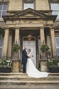 Bride and groom standing under door archway