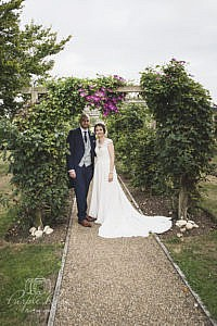 Bride and groom standing among flowers