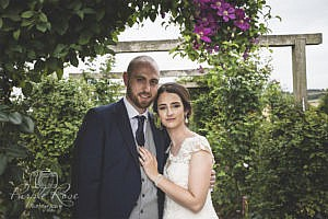 Bride and groom embracing under a floral arch
