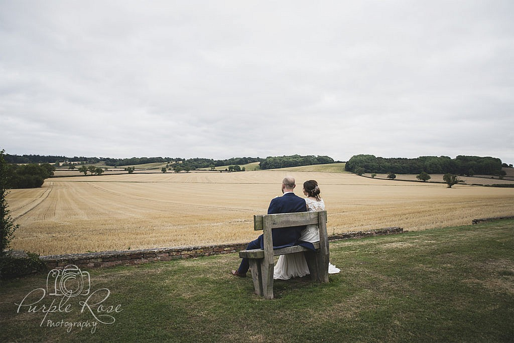 Bride and groom sat on bench looking out to open field