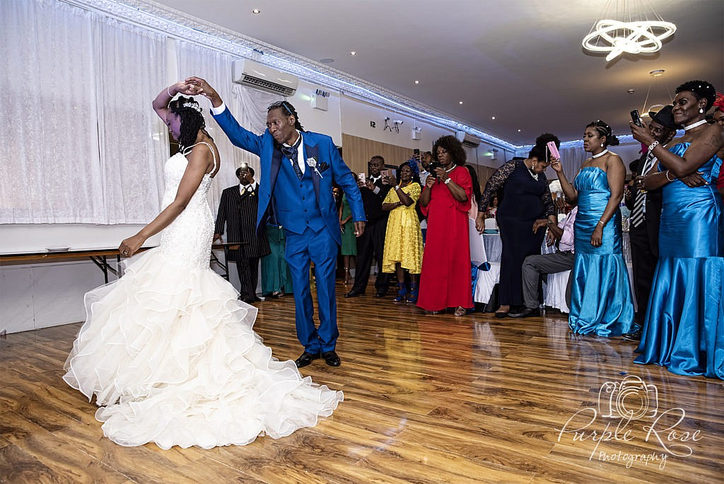 Groom twirling his bride on the dance floor