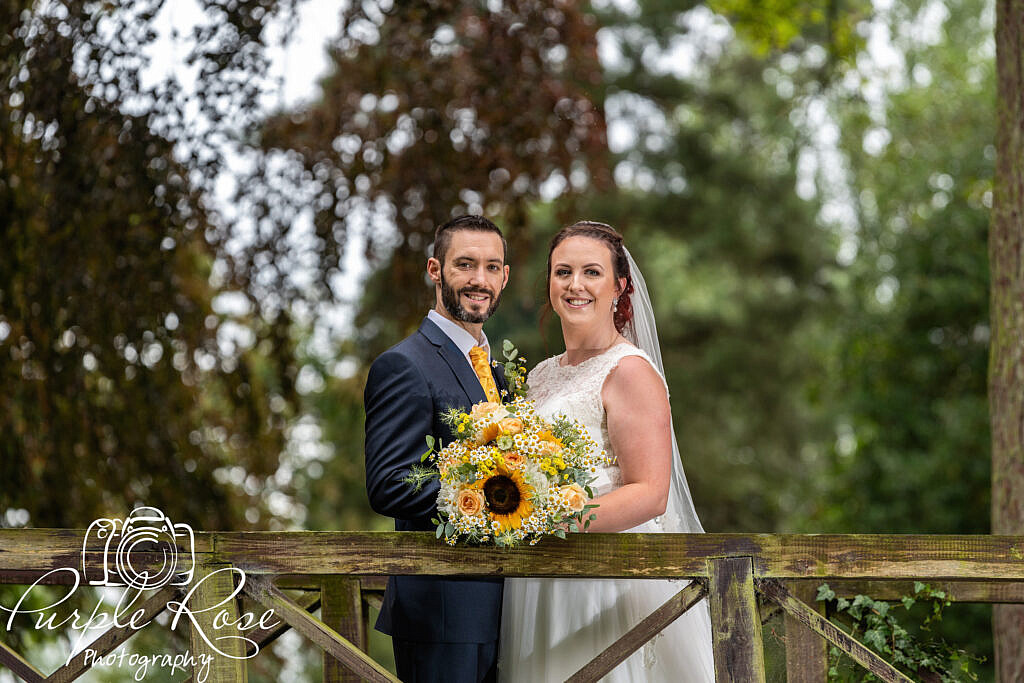 Bride and groom smiling on a bridge