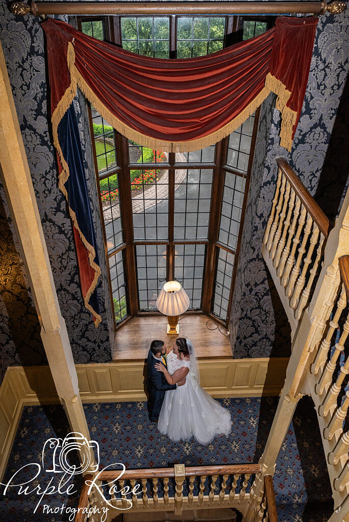 Bride and groom in front of a grand window