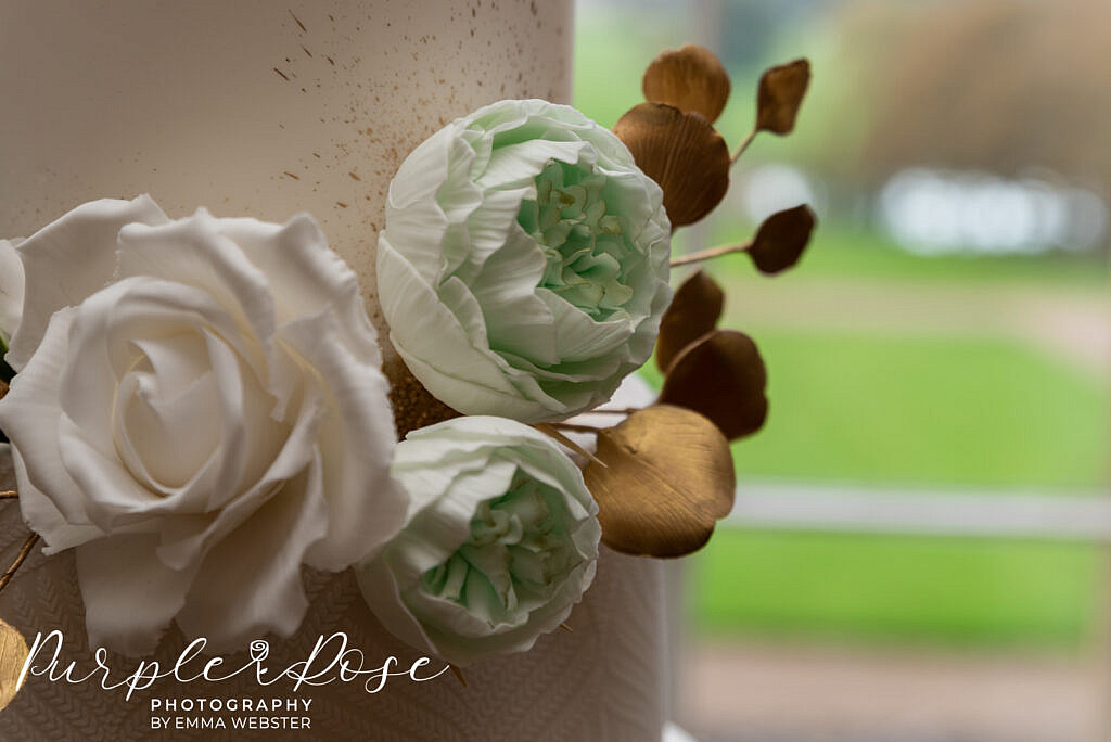 Intricate hand made flowers on a wedding cake in Kelmarsh Hall Northampton