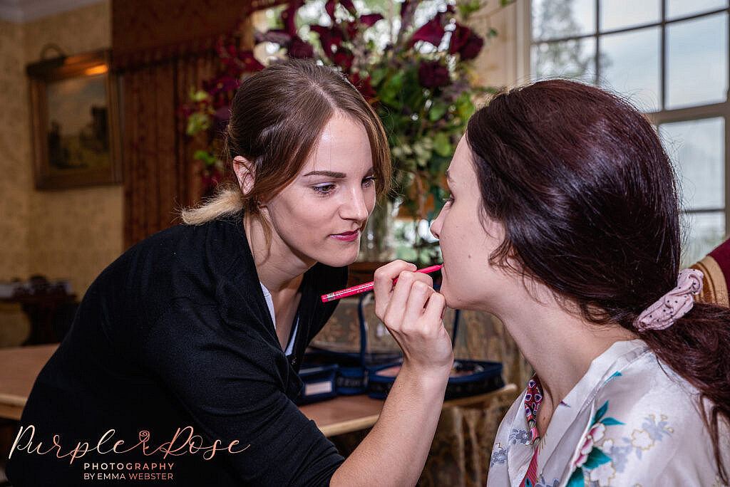 Make up artist applying makeup to a bridesmaid