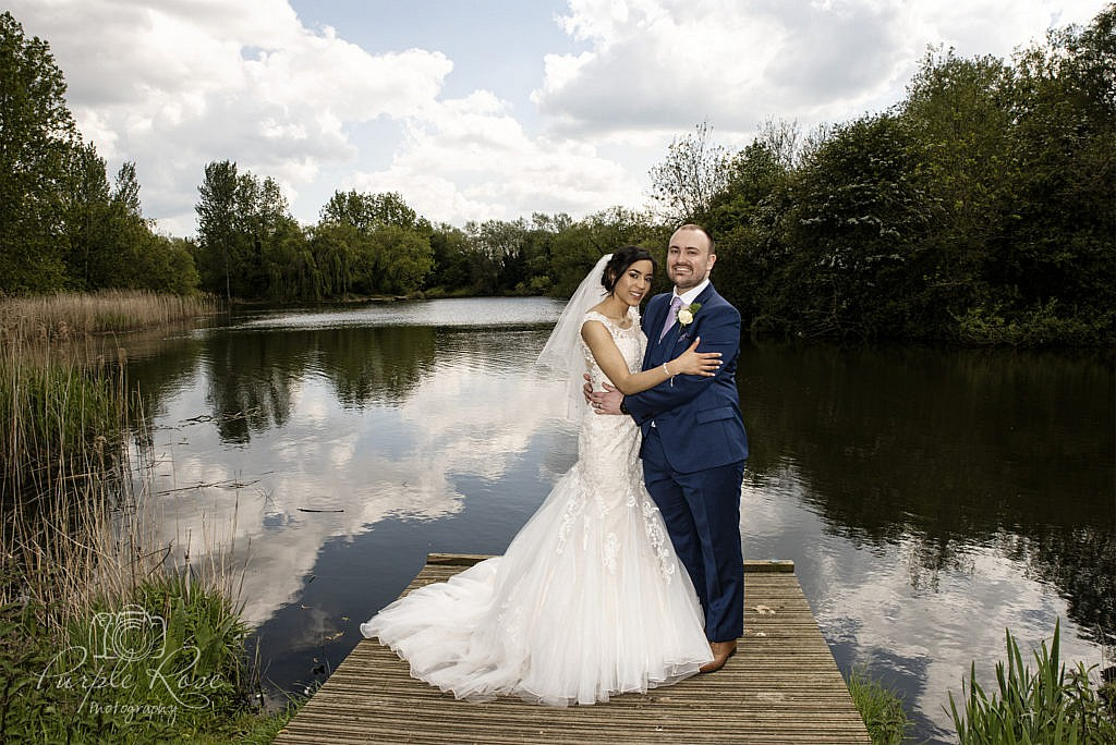 Bride and groom standing on a lakeside