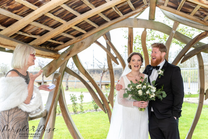 Bride and groom under a gazebo listening to a reading
