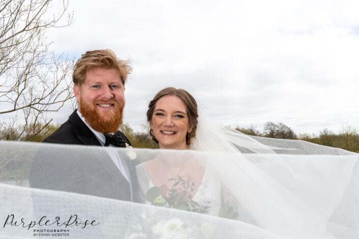 brides veil swirling around couple