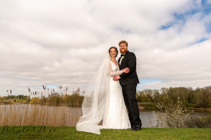 Bride and groom stood by a lake side