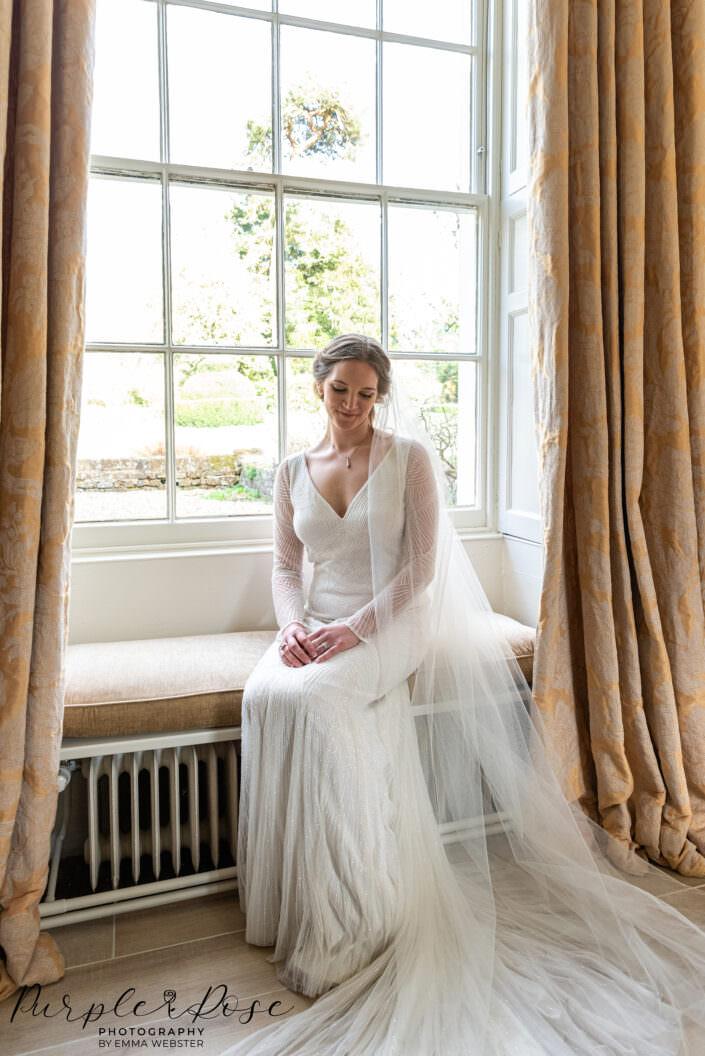 Bride sat by tall winddow