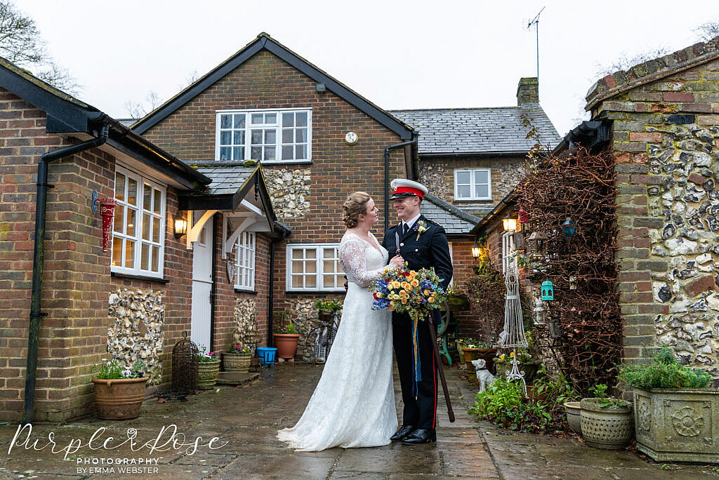 Bride and groom standing in a courtyard