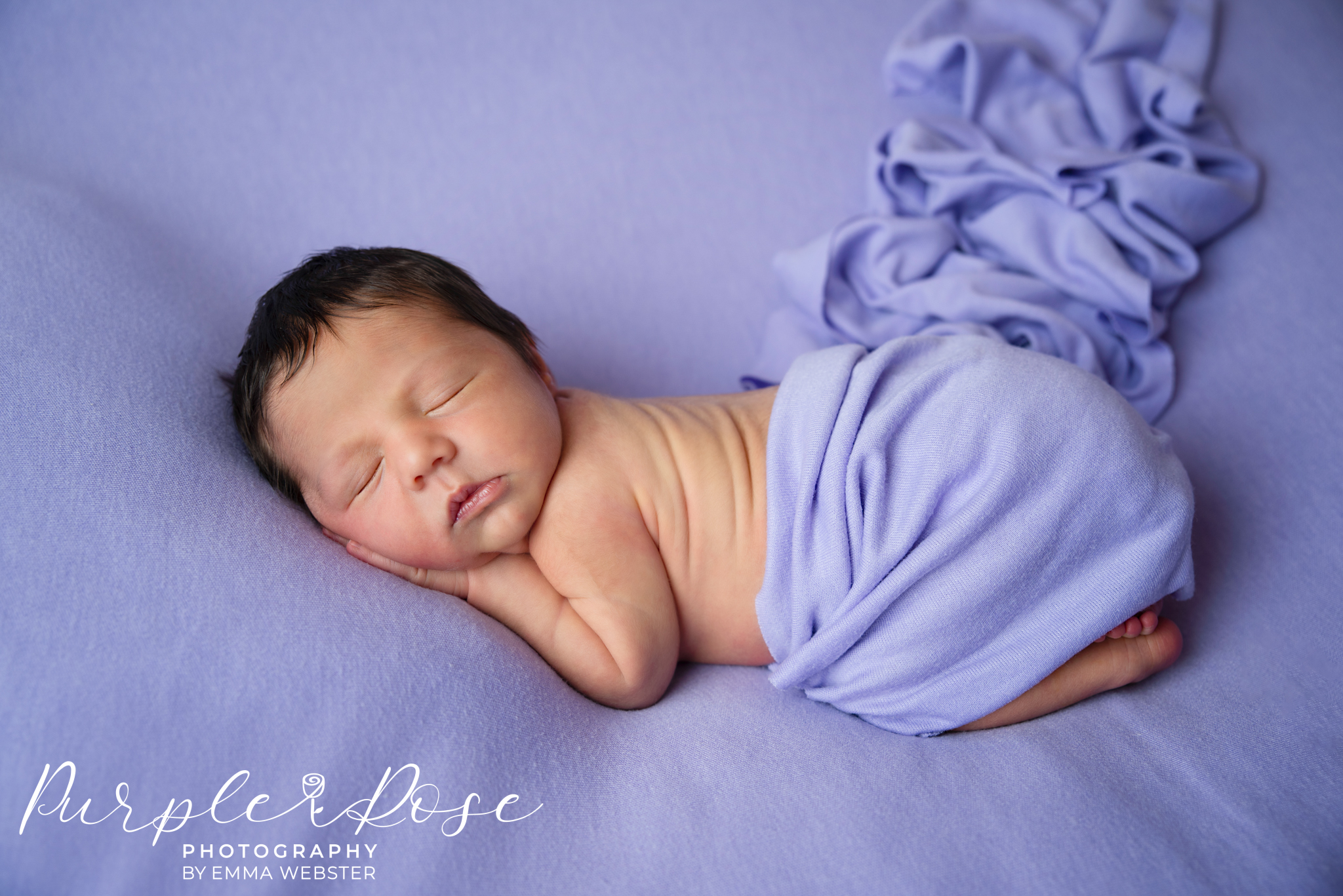 New born baby sleeping on a purple blanket