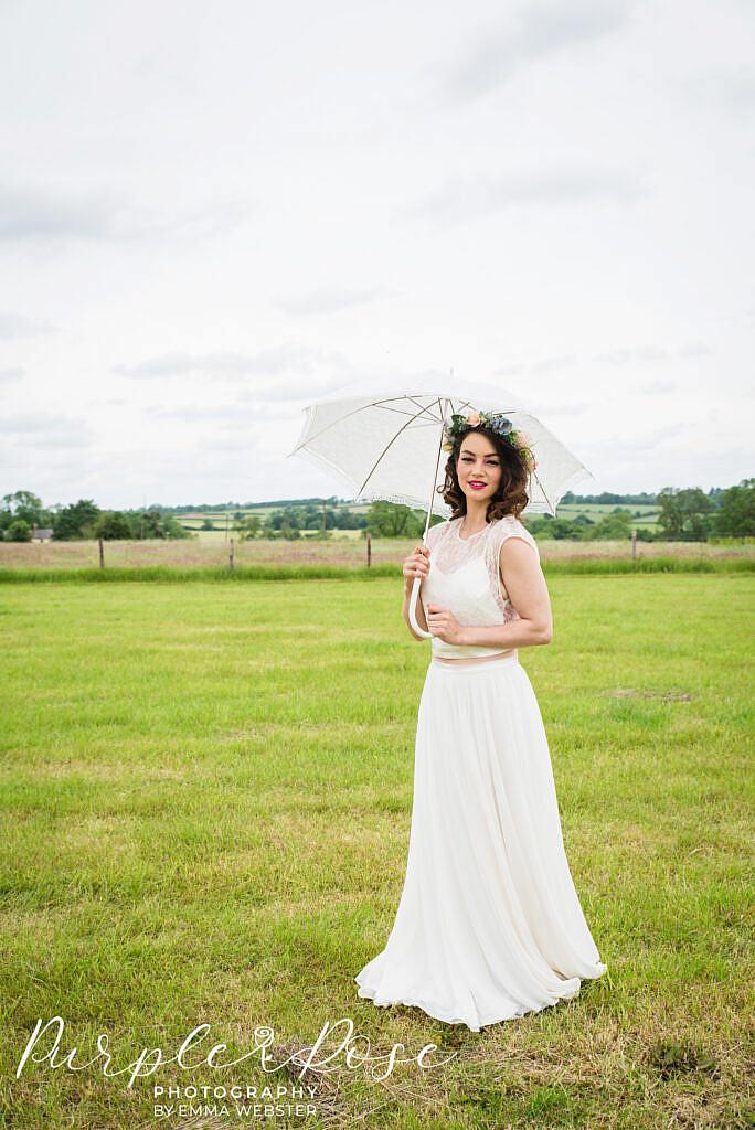 Bride sheltering under an umbrella