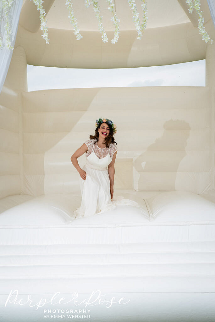 bride laughing on a bouncy castle