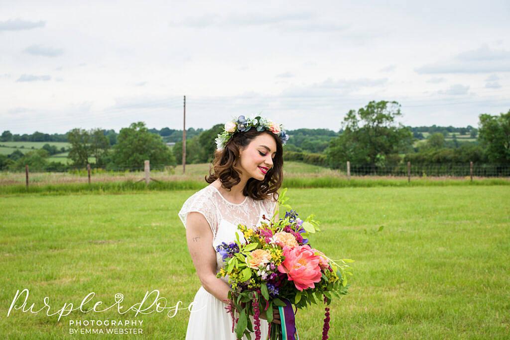 bride looking at her wedding bouquet