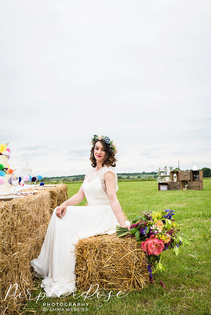 Bride sitting on a hay bale holding her flowers