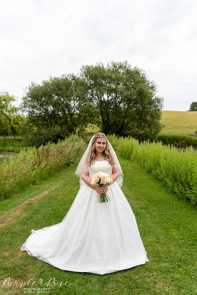 bride standing in venues gardens