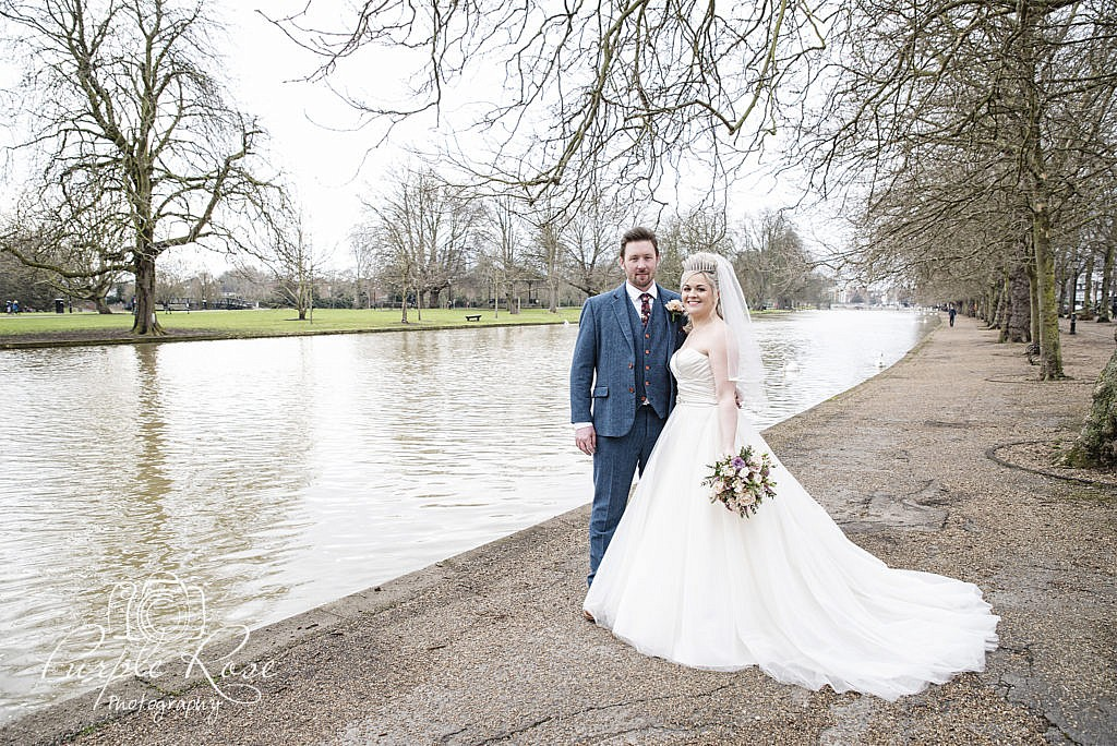Bride and groom Standing by Bedford river bank