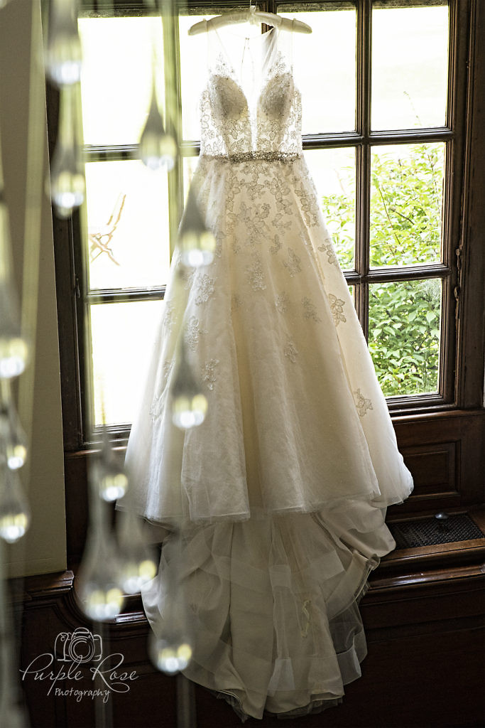 Wedding dress hanging in a window at Chicheley Hall